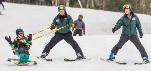 people skiing with adaptive equipment